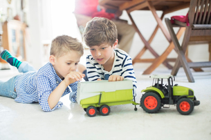 Brothers playing with toy tractor on floorの写真素材 [FYI02165550]