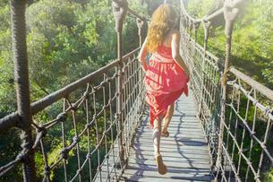 Woman walking on wooden rope bridgeの写真素材 [FYI02165553]