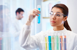 Woman in laboratory looking at vial with blue fluidの写真素材 [FYI02165583]