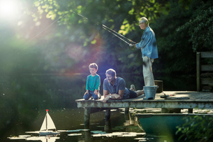 Boy fishing and playing with toy sailboat with father and grandfather at lakeの写真素材 [FYI02165640]