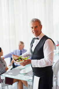 Portrait of waiter holding salad bowl, people at table in backgroundの写真素材 [FYI02165646]