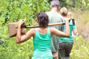 Rear view of woman wearing green tank top carrying shovel on shoulders through gardenの写真素材 [FYI02165669]
