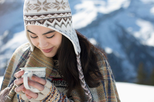 Smiling woman in knit hat drinking hot cocoa outdoorsの写真素材 [FYI02165688]