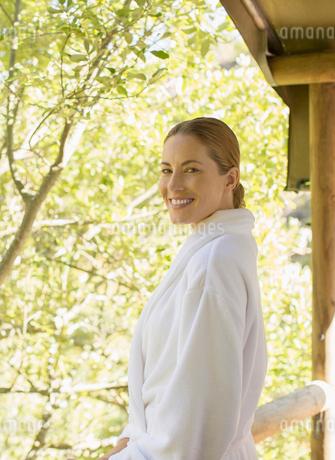 Woman wearing bathrobe on balconyの写真素材 [FYI02165710]