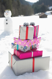 Stack of Christmas gifts in snowの写真素材 [FYI02165740]