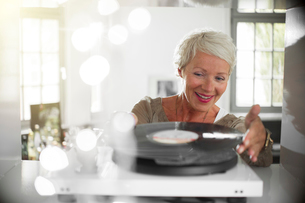 Older woman playing vinyl record on turntableの写真素材 [FYI02165758]