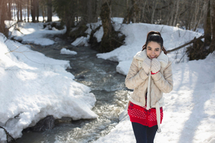 Portrait of smiling woman walking along snowy riverbankの写真素材 [FYI02165800]