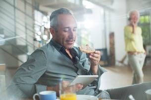 Older man using digital tablet at breakfast tableの写真素材 [FYI02165801]
