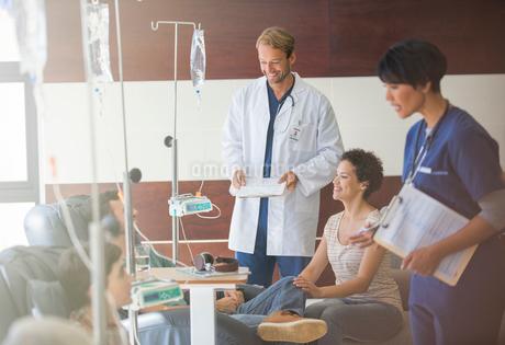 Doctors attending patients receiving intravenous infusion in hospitalの写真素材 [FYI02165892]