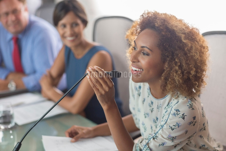 Beautiful woman sitting at conference table talking into microphoneの写真素材 [FYI02165894]