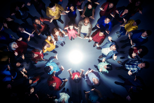 Business people forming circle around bright lightの写真素材 [FYI02165895]