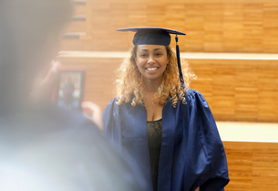 Female student in graduation gown posing for picture in university corridorの写真素材 [FYI02165898]