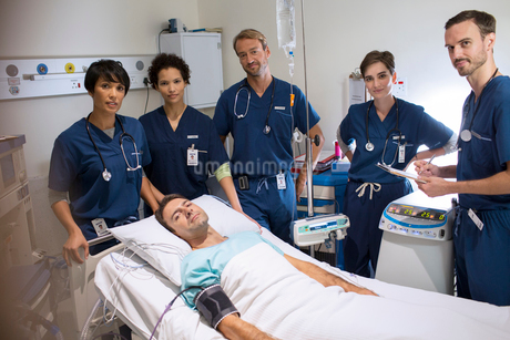 Team of doctors standing around smiling patient lying in bed in intensive care unitの写真素材 [FYI02165992]