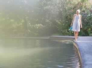 Woman walking by edge of poolの写真素材 [FYI02166007]