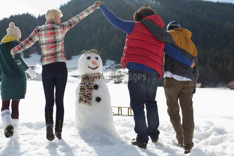 Friends playing around snowmanの写真素材 [FYI02166077]