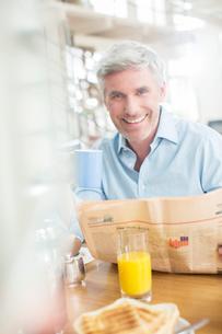 Older man reading newspaper at breakfast tableの写真素材 [FYI02166138]