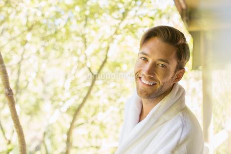 Man wearing bathrobe on balconyの写真素材 [FYI02166163]