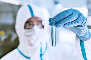 Close up of scientist in clean suit examining sample in test tubeの写真素材 [FYI02166181]