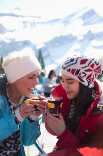 Friends in warm clothing drinking tea outdoorsの写真素材 [FYI02166192]