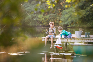 Boys fishing and playing with toy sailboat at lakeの写真素材 [FYI02166212]