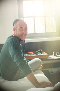 Older man listening to record player with headphonesの写真素材 [FYI02166217]