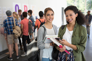 Portrait of two smiling female students holding books, other students in backgroundの写真素材 [FYI02166312]