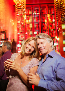 Portrait of smiling mature couple in bar, man in backgroundの写真素材 [FYI02166333]