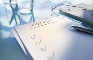 Close up of desk with,glass,glasses and note saying 'agenda',penの写真素材 [FYI02166402]