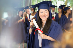 Portrait of smiling female student in graduation gown holding diplomaの写真素材 [FYI02166429]