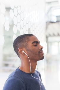 Portrait of young businessman listening to music on earphonesの写真素材 [FYI02166433]