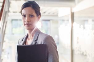 Portrait of businesswoman holding documents in office corridorの写真素材 [FYI02166435]