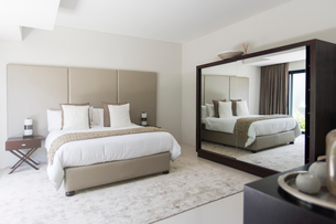 White and beige modern bedroom with double bed mirrorの写真素材 [FYI02166443]