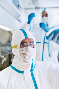 Scientist in clean suit examining test tube in laboratoryの写真素材 [FYI02166458]