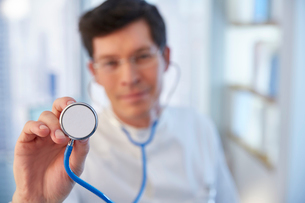 Man reaching towards camera with stethoscope in laboratoryの写真素材 [FYI02166480]
