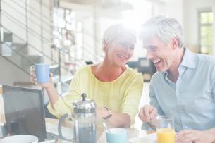 Older couple laughing together at breakfast table with laptopの写真素材 [FYI02166494]