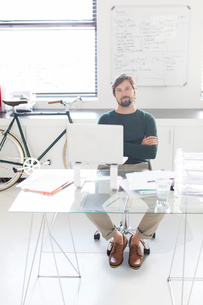 Portrait of man sitting with arms crossed behind glass desk in modern office, bicycle and whiteboardの写真素材 [FYI02166503]