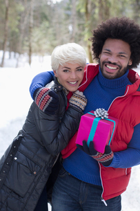 Portrait of couple with Christmas gift hugging in snowの写真素材 [FYI02166511]