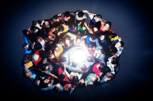 Diverse group in huddle around lightの写真素材 [FYI02166515]