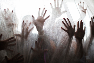 Silhouette of people raising hands behind transparent curtainの写真素材 [FYI02166544]