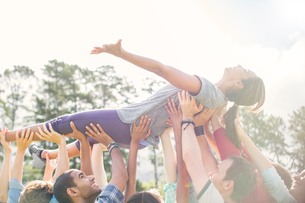 Carefree woman crowdsurfing supported by teamの写真素材 [FYI02166563]
