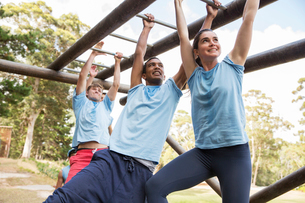 People crossing monkey bars on boot camp obstacle courseの写真素材 [FYI02166617]