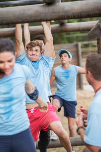 Determined people crossing monkey bars on boot camp obstacle courseの写真素材 [FYI02166633]