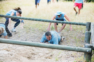 People crawling under net on boot camp obstacle courseの写真素材 [FYI02166641]