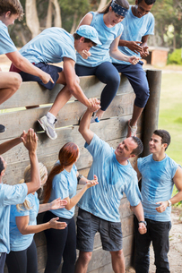 Teammates helping each other over wall on boot camp obstacle courseの写真素材 [FYI02166650]