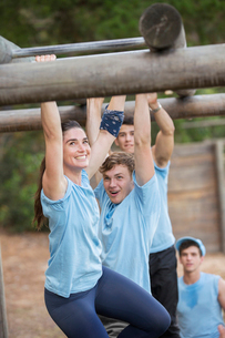 Smiling woman crossing monkey bars on boot camp obstacle courseの写真素材 [FYI02166652]