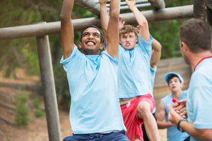 Determined men swinging on monkey bars on boot camp obstacle courseの写真素材 [FYI02166662]