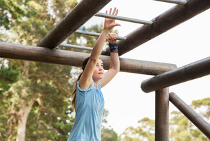 Determined woman crossing monkey bars on boot camp obstacle courseの写真素材 [FYI02166664]
