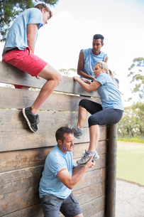 Teammates helping woman over wall on boot camp obstacle courseの写真素材 [FYI02166672]