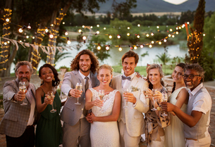 Portrait of young couple with guests toasting with champagne during wedding reception at duskの写真素材 [FYI02166677]