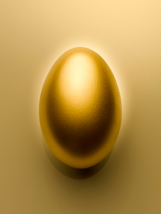Overhead view of golden egg on gold background still lifeの写真素材 [FYI02166679]